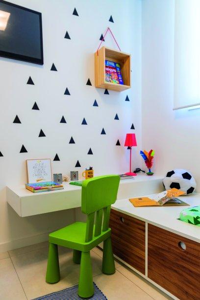 """""""Queríamos uma atmosfera lúdica para o dormitório infantil"""", diz Fabiana. Assim, o conjunto de escrivaninha e cama com gavetões ganha ainda mais graça combinado com o adesivo de parede (Kit Triângulo Preto, com 36 peças de 7 x 7 cm. Kola. Projeto das arquitetas Fabiana Silveira e Patrícia de Palma, do escritório SP Estudio."""