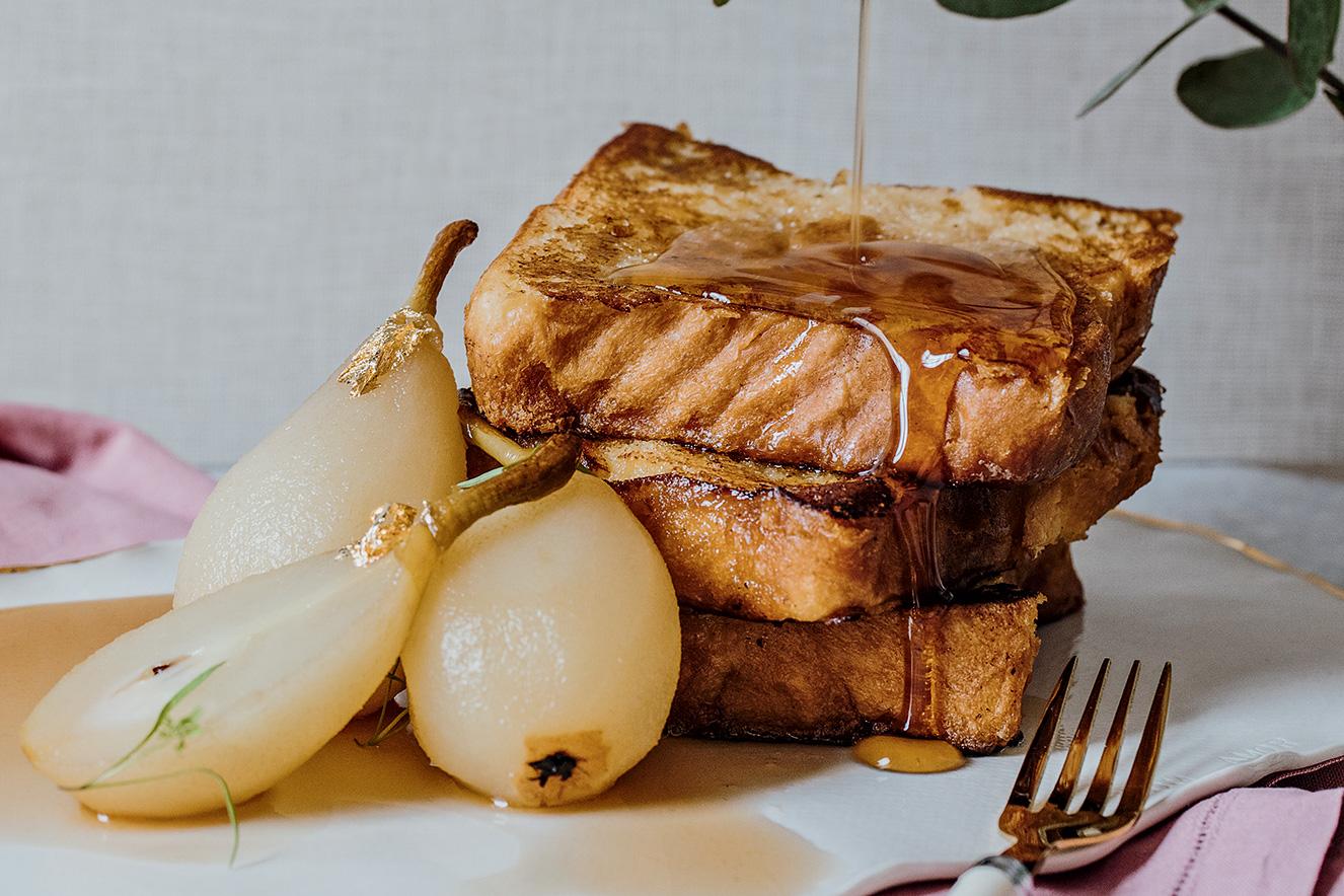 Três fatias de pão empilhadas e cobertas por mel estão ao lado de três peras ao vinho e sem casca. À frente, aparece um garfo