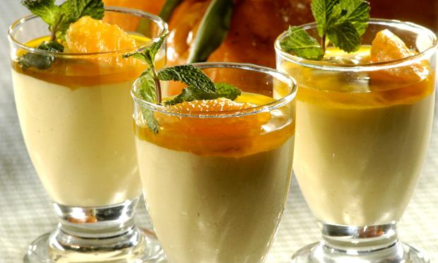 Três taças de sobremesa com musse com amarelo pastel coberto por calda de cor laranja e decorado com folhinhas verdes. Ao fundo, desfocada, aparece uma tangerina