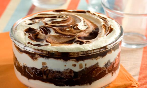 Uma travessa redonda de vidro com pavê, que tem tons de chocolate e creme branco