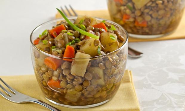 Em um copo de vidro está a salada de lentilha com pedaços de azeitona, vagem e cenoura. Ao fundo, desfocado, aparece outro copo e um garfo.