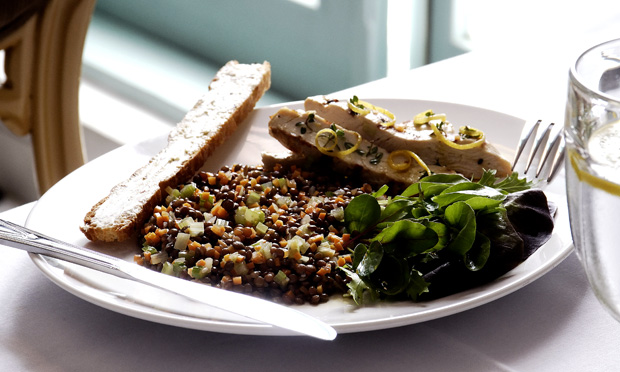 Sobre um prato branco está a salada de lentilha com pedaços de frango e folhas verdes
