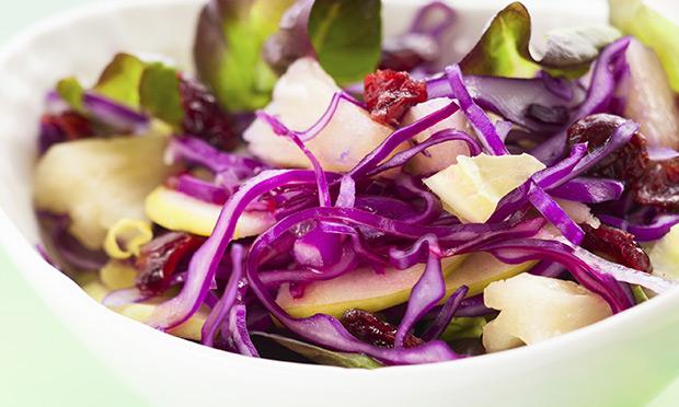 Em uma tigela branca está uma salada com repolho fatiado fino, pedaços de palmito e sementes de romã