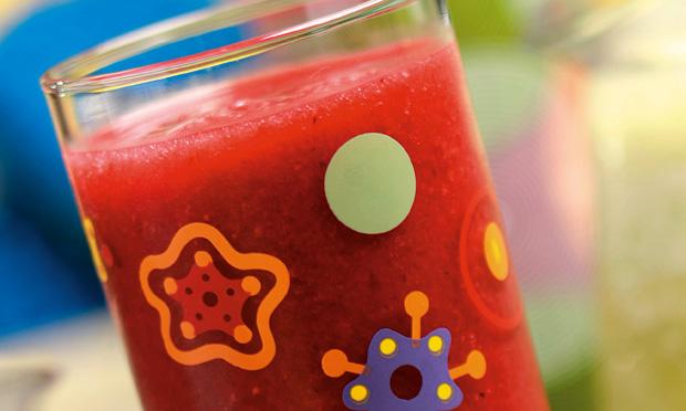 Um copo de vidro com desenhos coloridos cheio de suco de cor vermelha aparece sobre fundo desfocado azul e verde