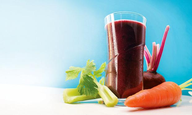 Um copo de vidro cheio com suco de cor roxa é cercado por dois pedaços de salsão, uma cenoura e uma beterraba