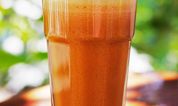 Um copo de suco de cor laranja cheio aparece sobre um fundo desfocado verde