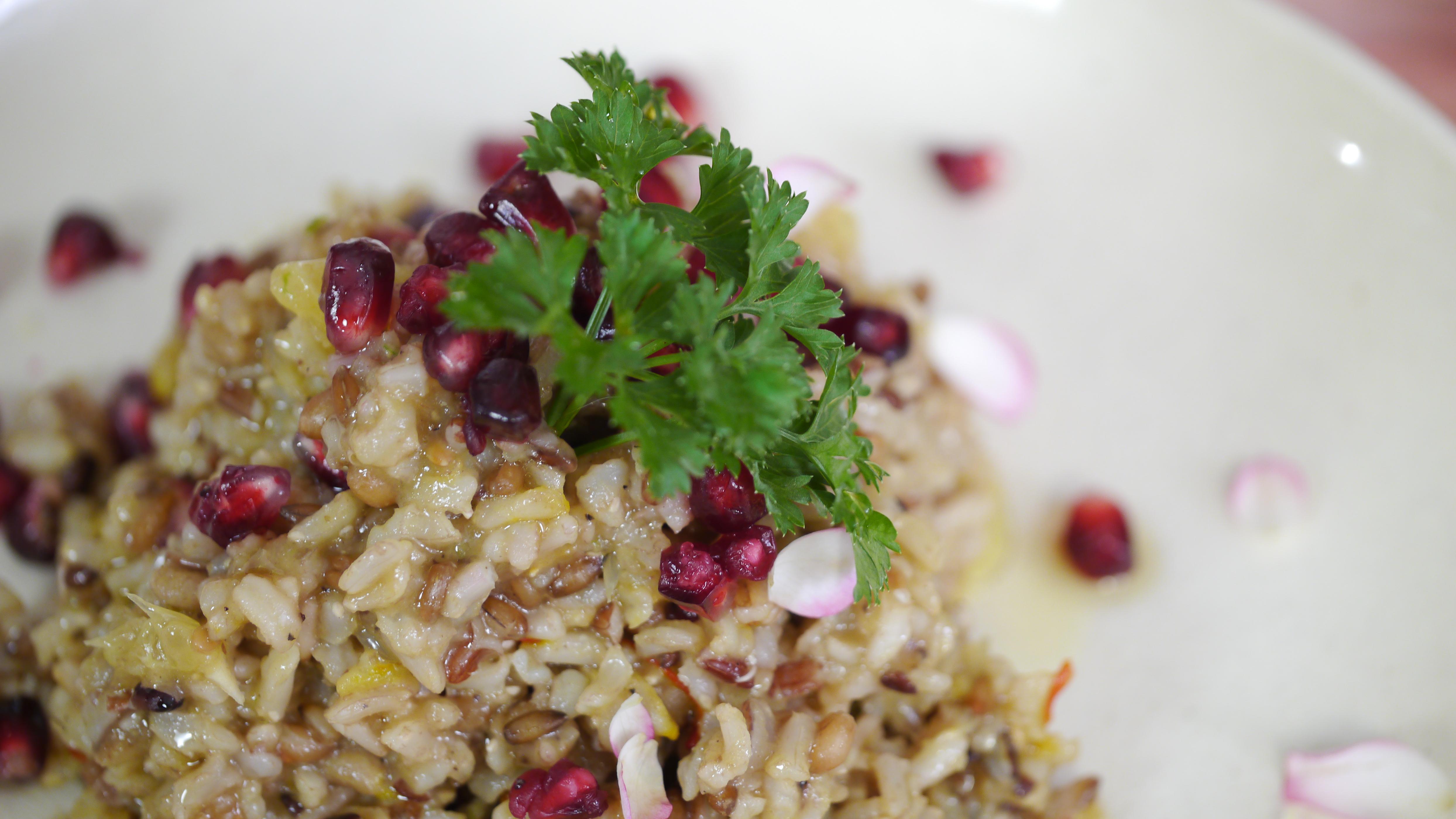 Na foto, há uma mistura de arroz e trigo cozidos com sementes de romã e uma folha de salsinha no topo, para decorar