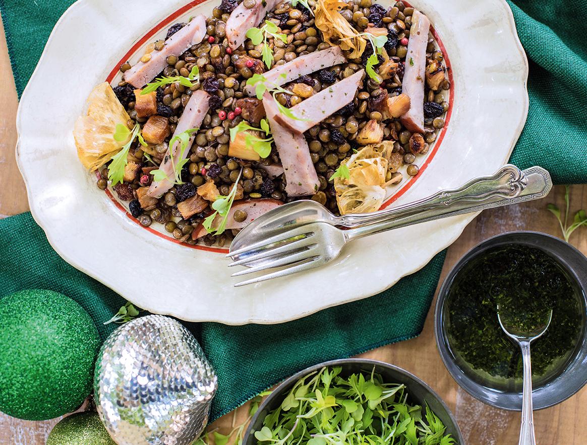 Em um prato branco, há uma salada de grãos com pedaços de tender e abacaxi. Um garfo está apoiado sobre o prato.