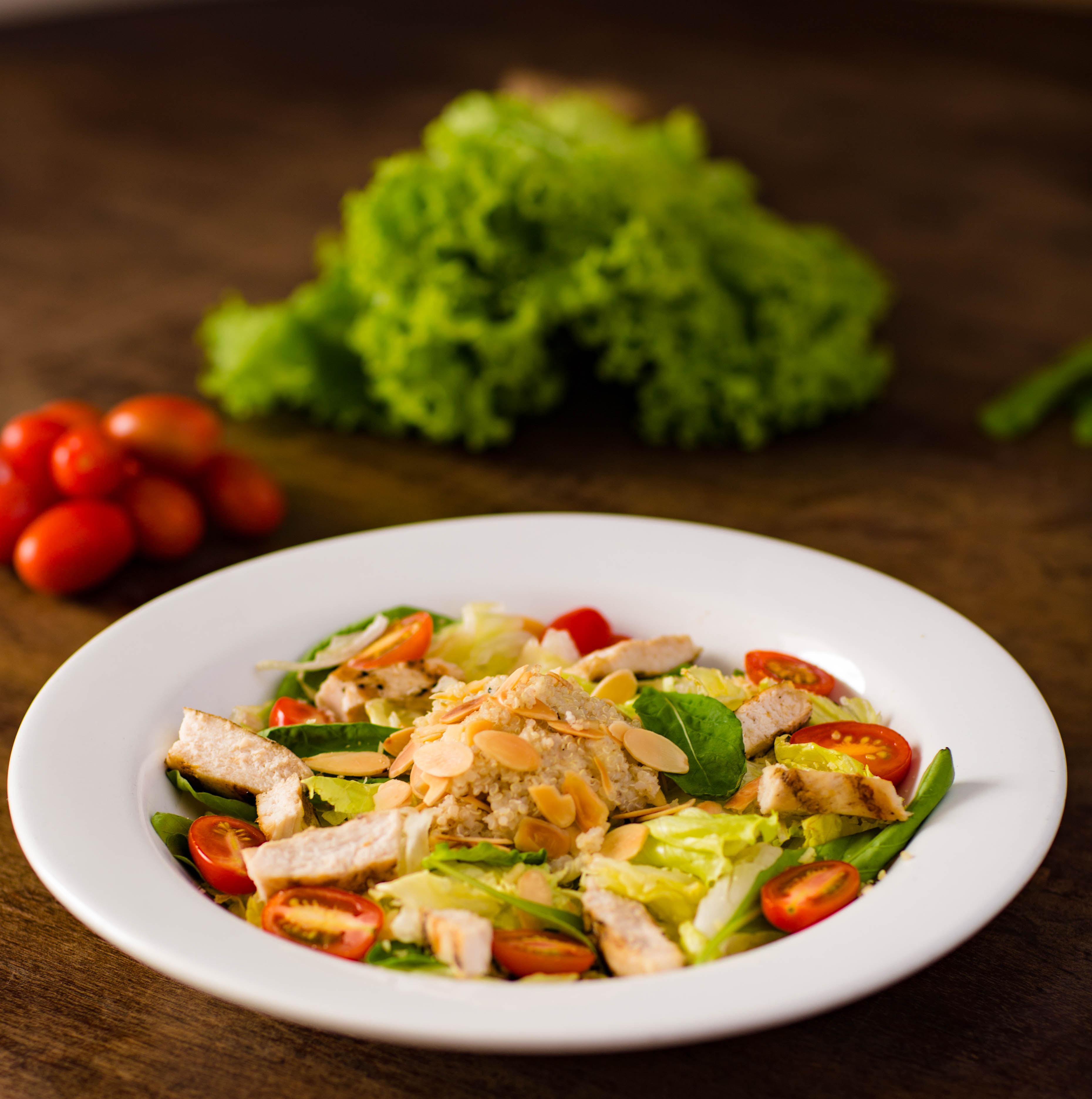 Em um prato branco fundo, há uma salada com folhas verdes, tomates, pedaços de frango e quinoa. No fundo, desfocado, aparece um pé de alface e tomates-cereja