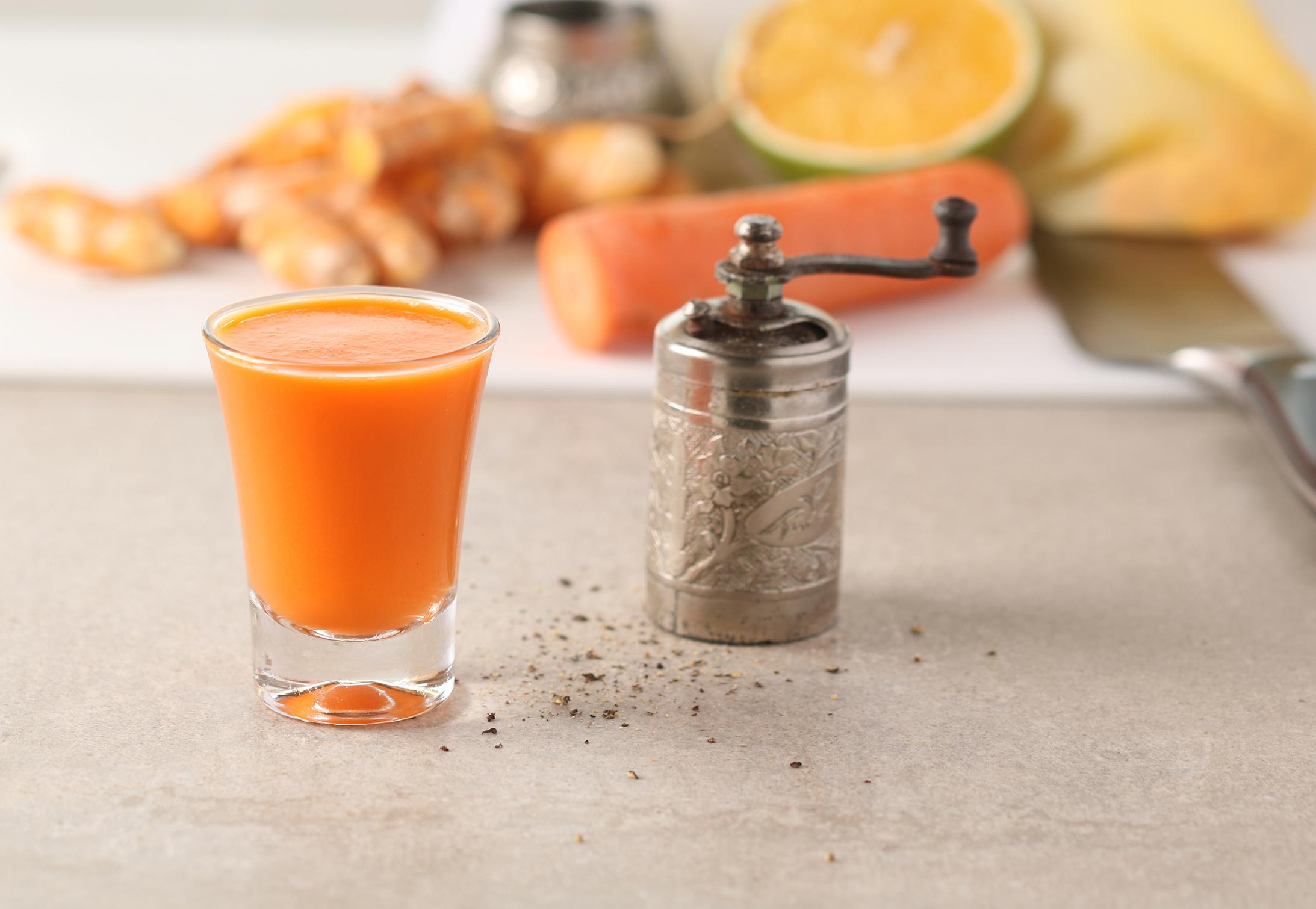 copinho de shot cheio de suco de cor laranja sobre uma superfície de cimento queimado aparece ao lado de um moedor de pimenta prateado. Ao fundo, aparece uma cenoura descascada, pedaços de gengibre, meia laranja e uma espátula