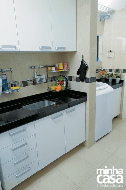 <span>Os armários preenchem as paredes laterais, aproveitando o formato alongado da cozinha. De granito preto são marcos, a bancada se repete na área de serviço. Projeto da designer de interioresGabriela Alencar.</span>