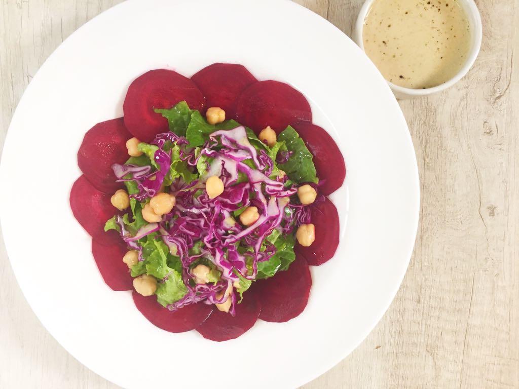 Em um prato branco aparecem diversas fatias de beterraba cortadas bem finas, como um carpaccio. No meio, uma salada de grãos, folhas verdes e repolho