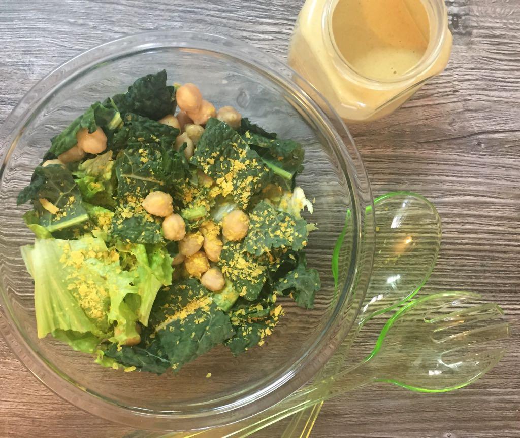 Em uma tigela de vidro, há uma salada de folhas verdes com grão de bico. Ao lado, há um pote com molho de tahine. Sobre a superfície de madeira, há duas colheres de plástico esverdeadas