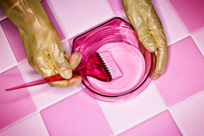 Mãos com luvas rosas preparando tinta para pintar o cabelo