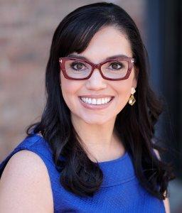 mulher de cabelo preto e vestido azul, sorrindo.