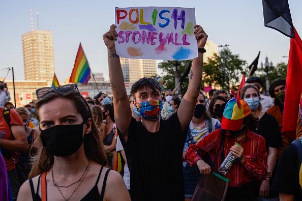"""Ativista com máscara protetiva colorida segura ao alto cartaz escrito """"Stonewall polonês"""", em inglês e em letras coloridas."""