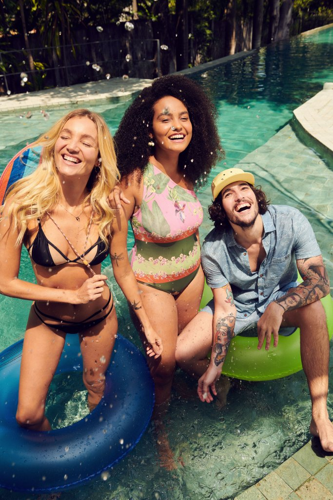 Duas mulheres e um homem sorrindo e posando para foto. Elas estão em pé e ele sentado em uma boia. Todos estão dentro de uma piscina. A da esquerda usa um biquíni preto. A do meio, um maiô rosa e verde. O homem, na direita, está com um conjunto azul