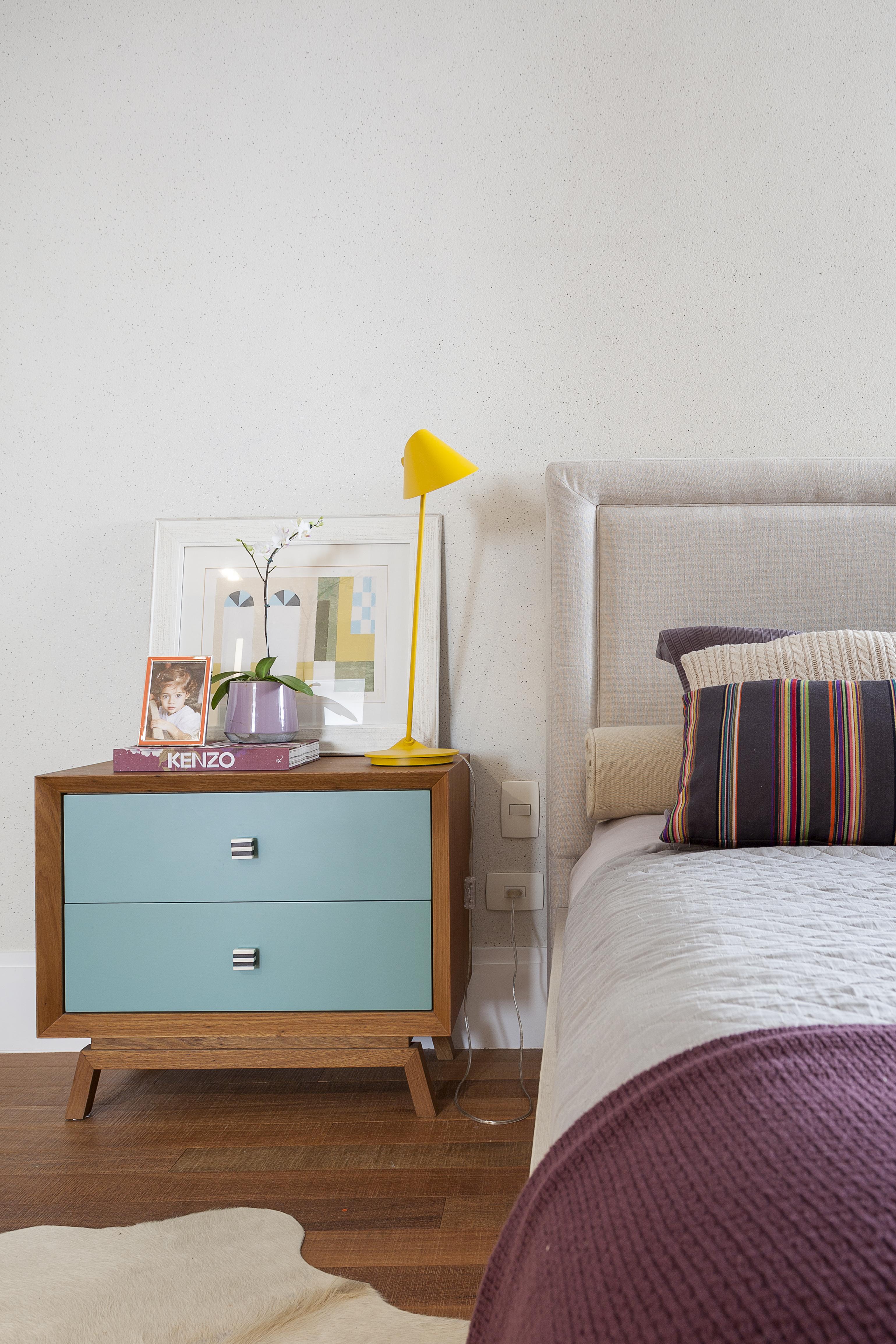 No canto esquerdo, aparece uma mesa de cabeceira de madeira com as gavetas azuis. Sobre ela, há uma luminária de mesa amarela, alguns porta-retratos e um quadro apoiado na parede. Ao lado, aparece metade da cama, que tem cabeceira estofada, almofadas listradas de laranja e marrom e a colcha branca. No pé da cama, há uma colcha roxa