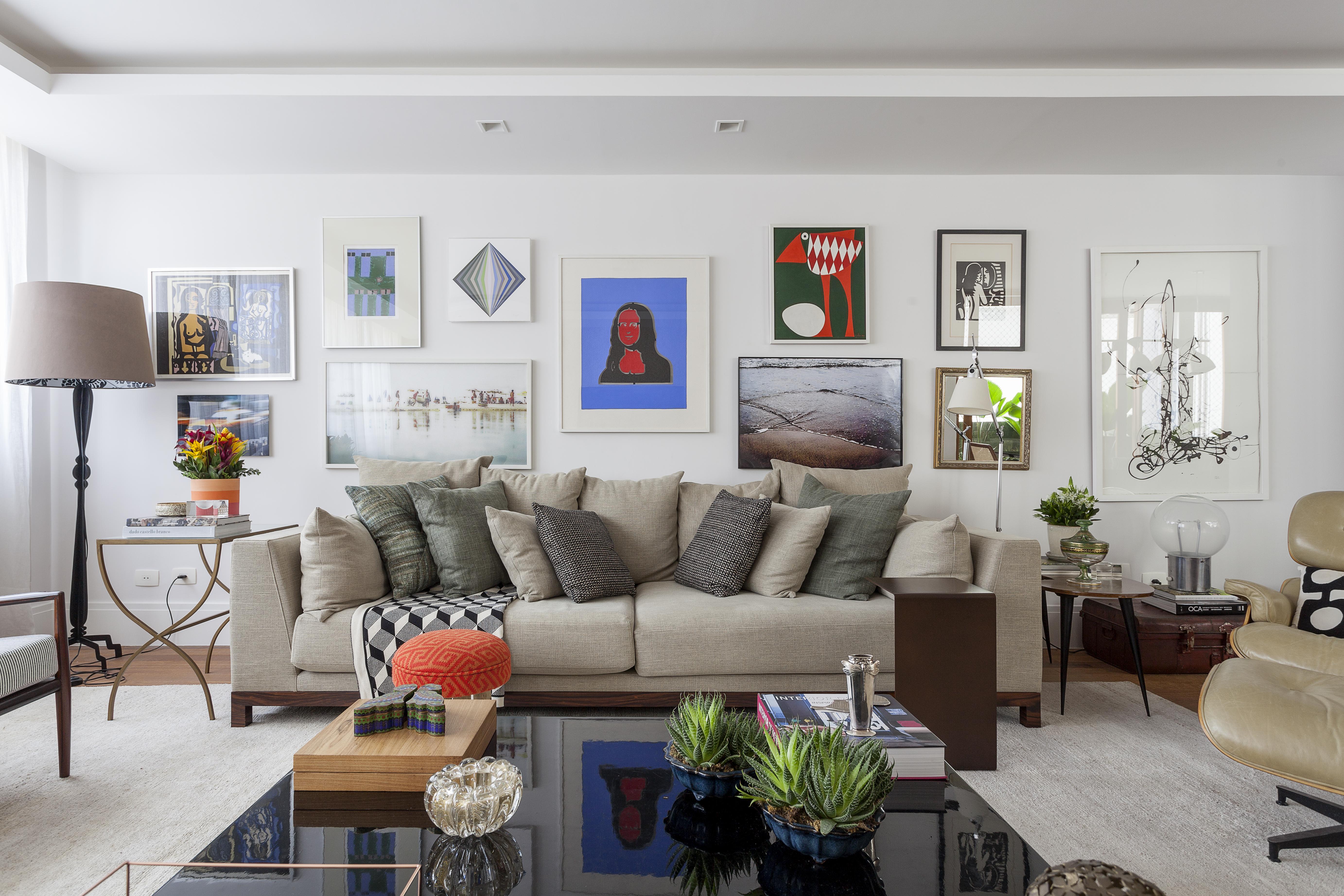 Em primeiro plano aparece uma mesa de centro de laca preta bastante grande com vasos e objetos decorativos sobre ela. Ao fundo, um sofá de linho cru com almofadas verdes e uma parede estilo gallery wall, com diversos quadros