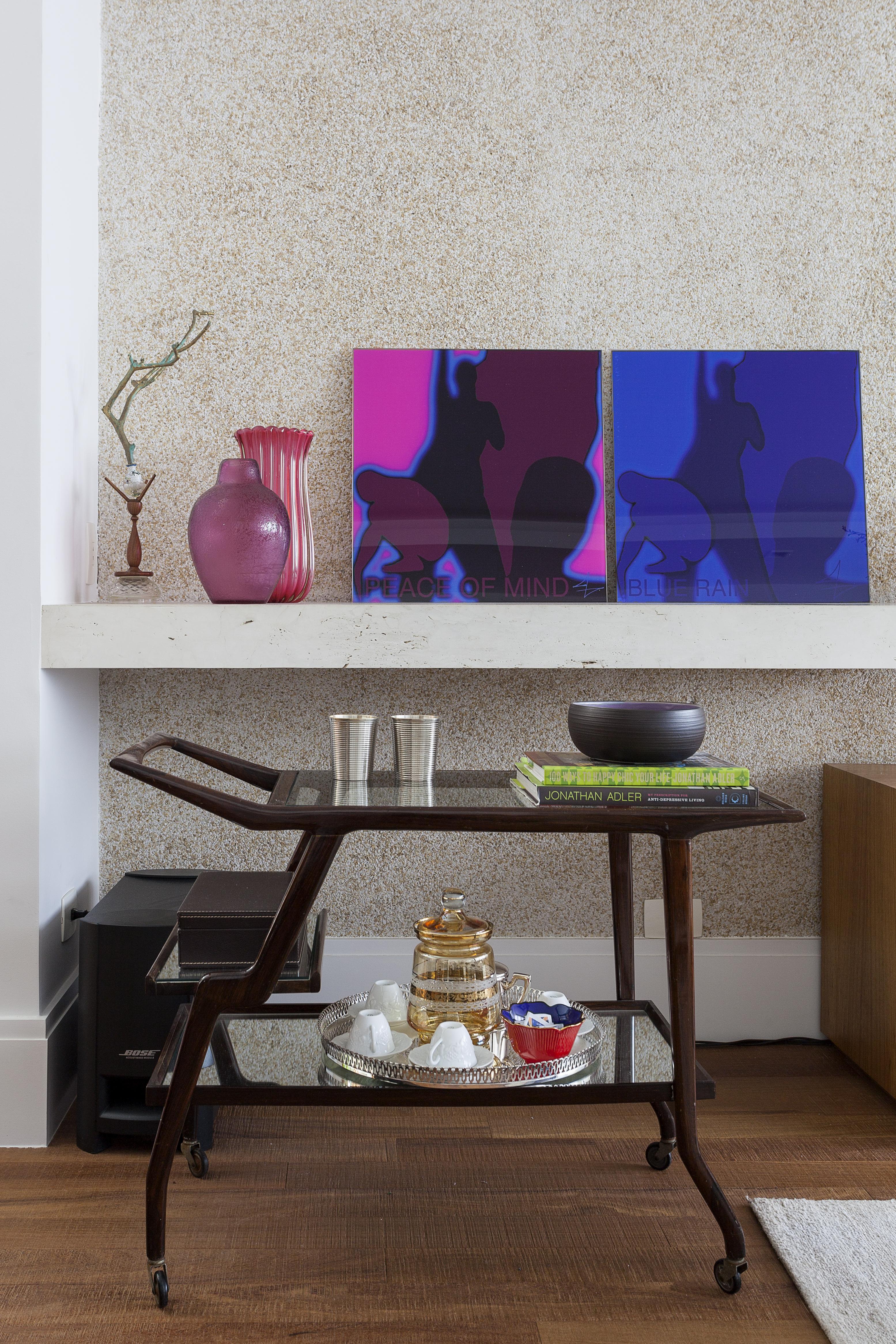 Em um ambiente claro, um carrinho de bar de madeira tem copos, uma cerâmica e algumas embalagens de vidro. Ao fundo, em uma prateleira, há dois quadros, um rosa e um azul, e alguns vasos cor de rosa