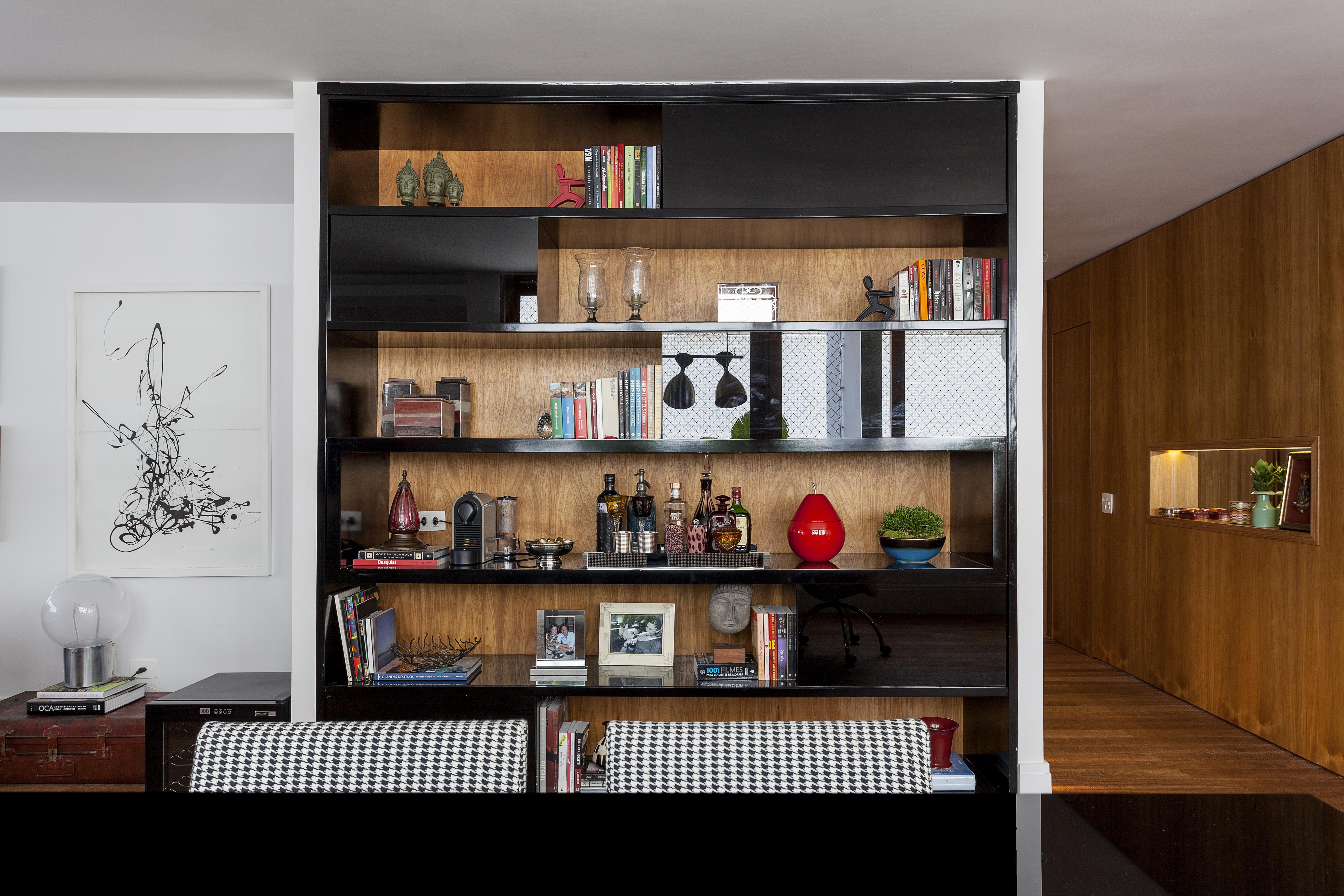 Na foto, aparece estante de madeira com portas pretas. Há vários objetos na estante, como livros, vasos e enfeites