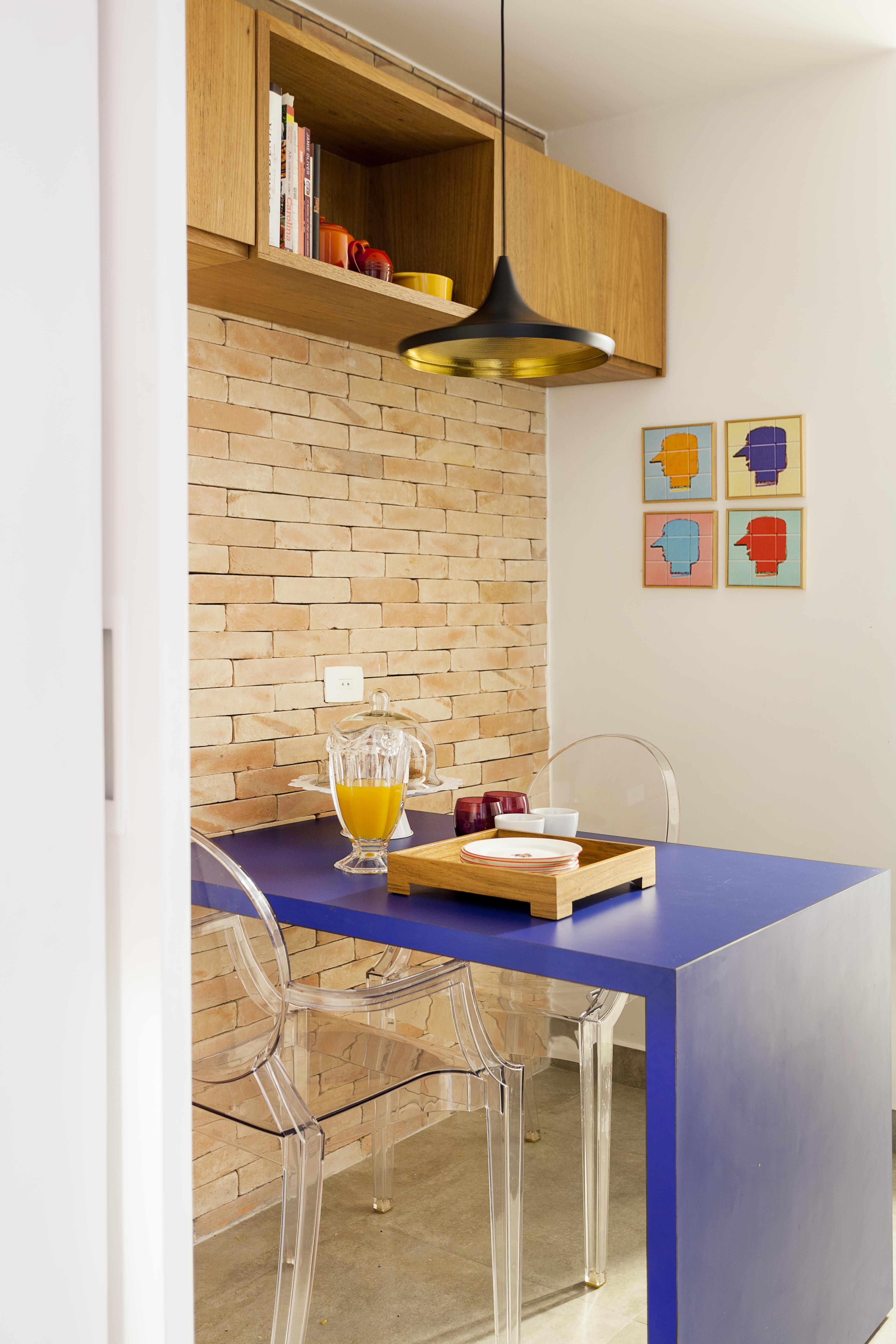 Na foto, em diagonal, é retratada uma cozinha, com mesa azul e cadeiras transparente. A parede ao fundo é de tijolos aparentes. Há um quadro colorido na paredes. O pendente preto e dourado aparece sobre a mesa, que tem uma bandeja de madeira e jarra de vidro com suco de laranja.