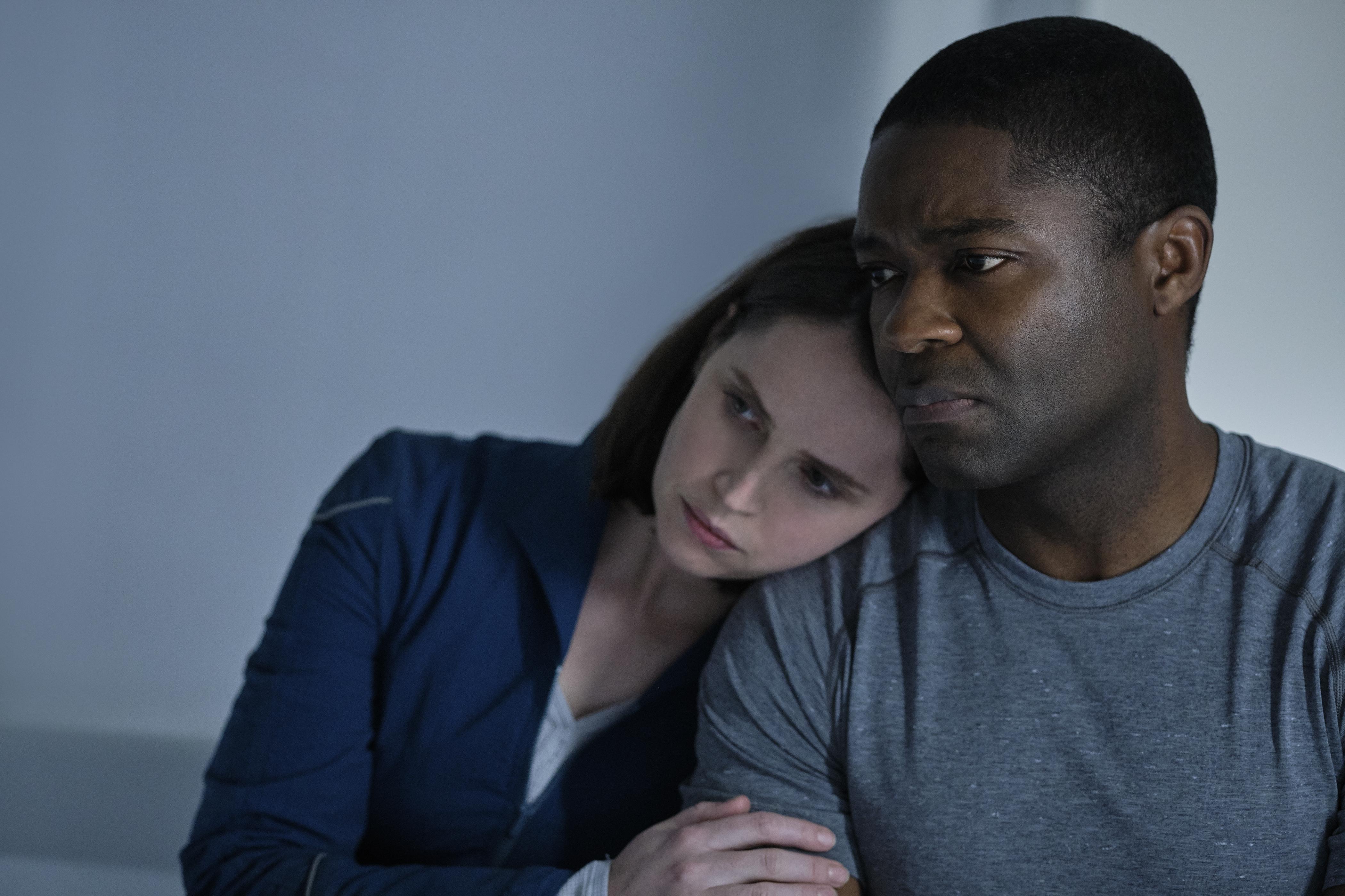 Mulher com roupa azul marinho está encostada sobre o ombro de um homem vestido com blusa cinza