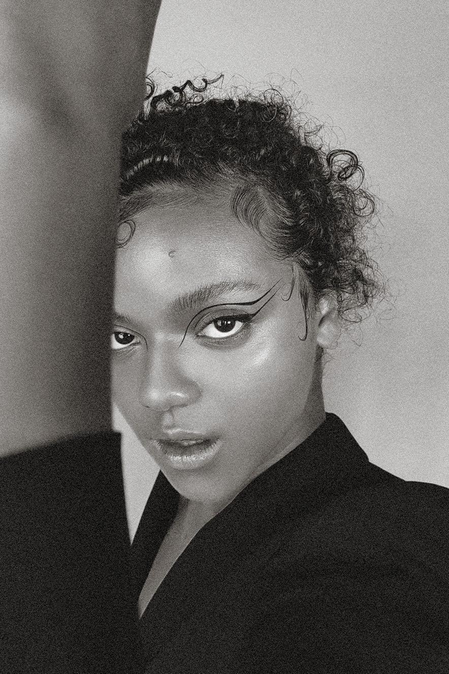 Mulher negra olha para a câmera. Ela tem no olho um desenho feito com delineador