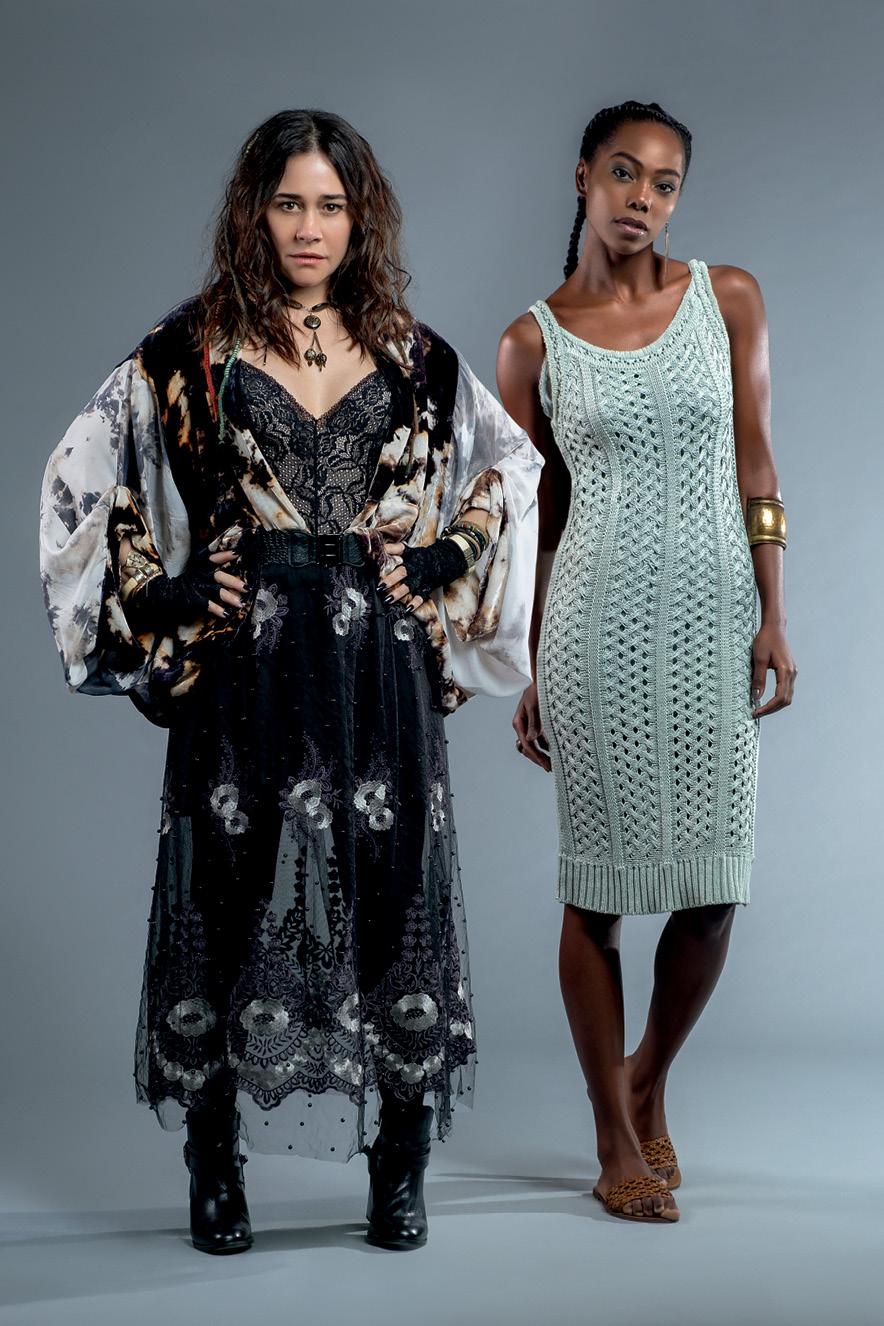 Duas mulheres posam para a câmera. Uma, branca, com o cabelo castanho e solto, usa um vestido fluido preto florido. Ela está com as mãos na cintura. A outra, negra, com o cabelo preso em duas tranças, está com um vestido verde.