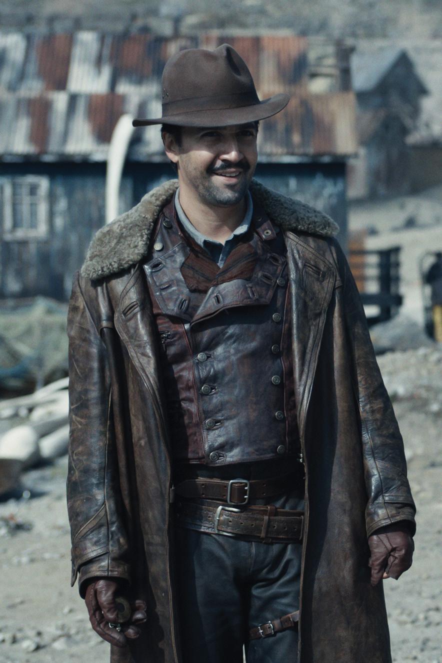 Homem com roupas de couro e chapéu caminha em cenário de fazenda antiga