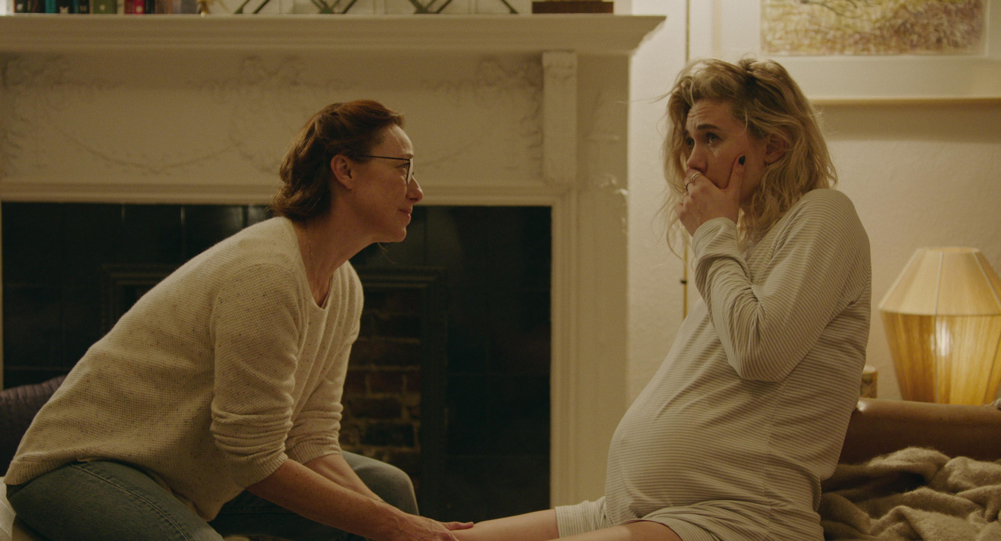 Duas mulheres sentadas olham uma para outra. Uma delas está grávida e com a mão na boca.