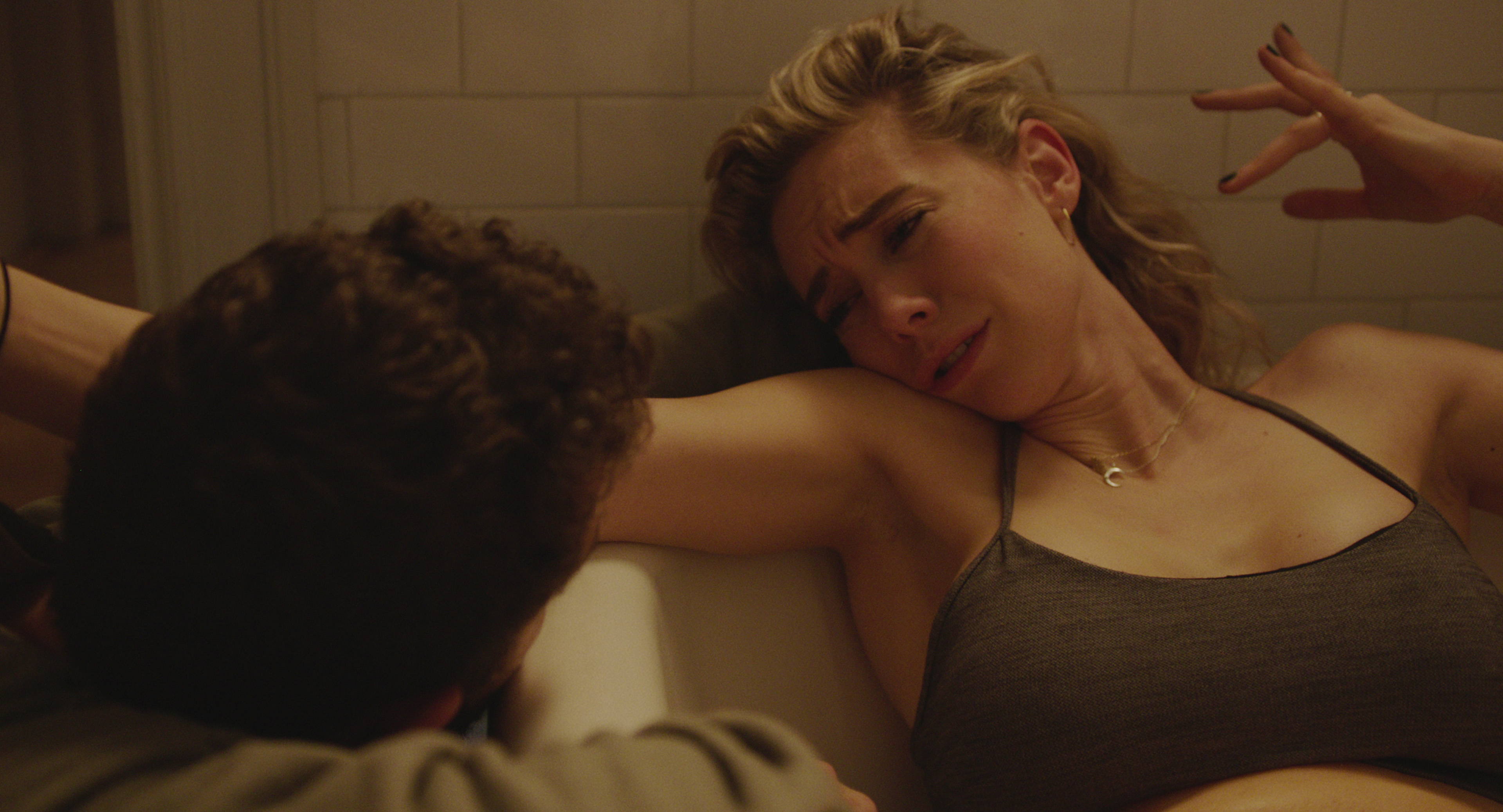 Uma mulher loira está deitada dentro de uma banheira, olhando para um homem, do lado de fora