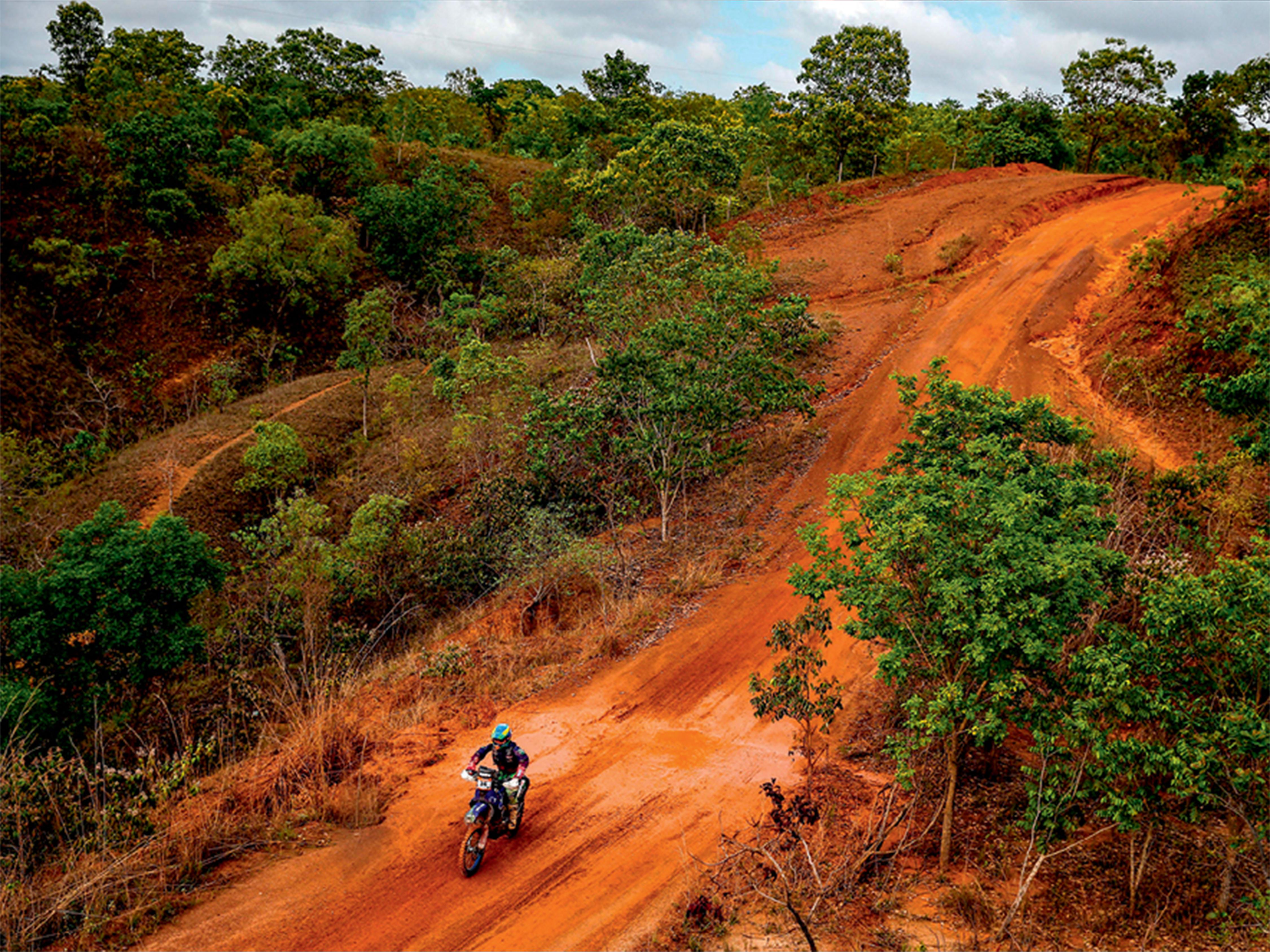 Uma faixa aberta em meio à vegetação vira pista no cenário de terra, com chão vermelho. Uma moto, pilotada por uma mulher, aparece no centro da pista