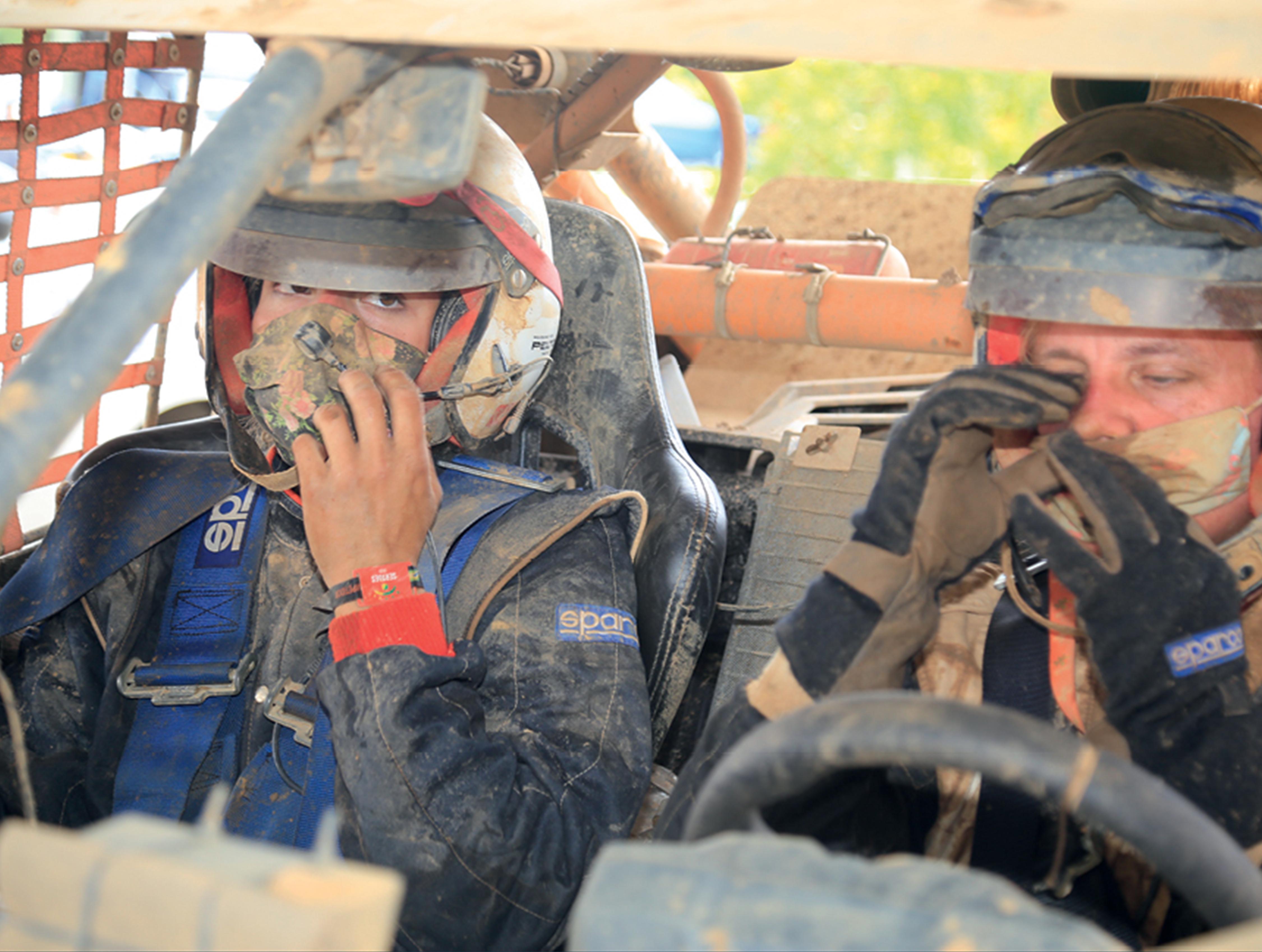 Duas mulheres estão sentadas nos bancos da frente do veículo. Elas estão com o uniforme, máscara e capacete, então só é possível enxergar os olhos delas. Elas e a superfície do carro estão sujas de terra e poeira levantadas na corrida.