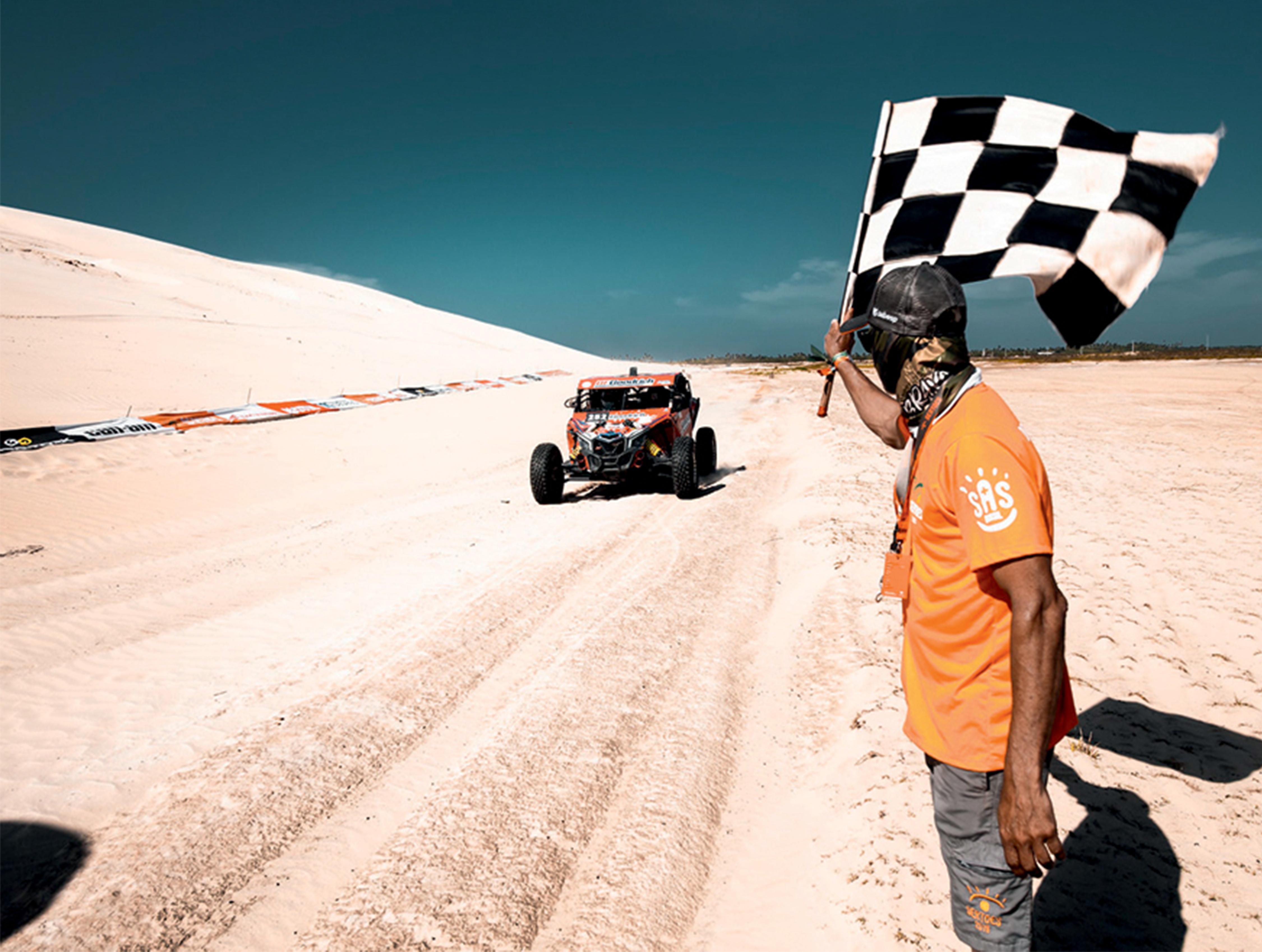 Em um terreno arenoso bem claro, um carro corre e se aproxima da bandeirada, dada por um homem de camiseta laranja