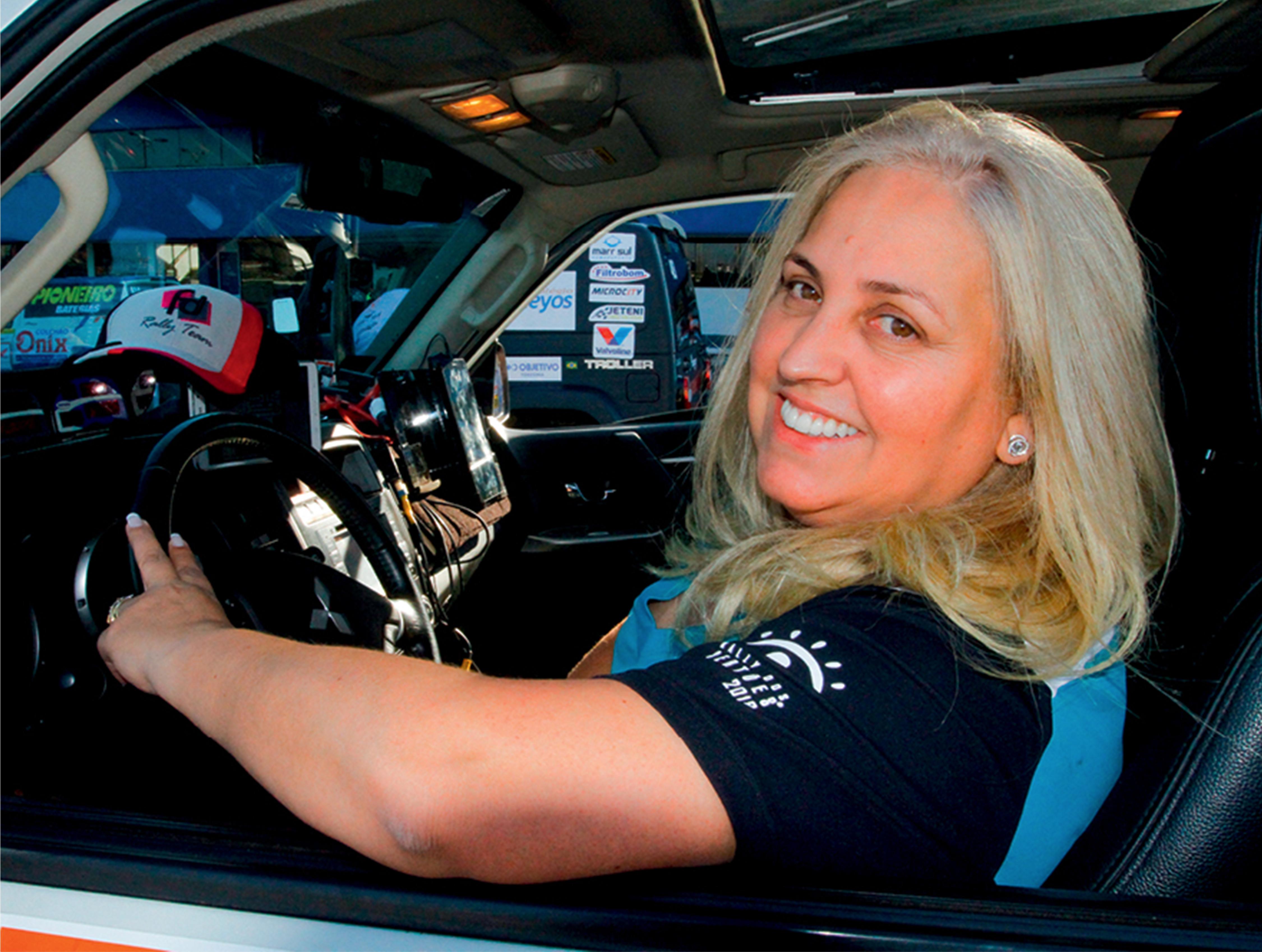 Mulher branca com cabelos loiros sorri para a foto. Ela está sentada dentro de um carro e com o braço apoiado na janela aberta.