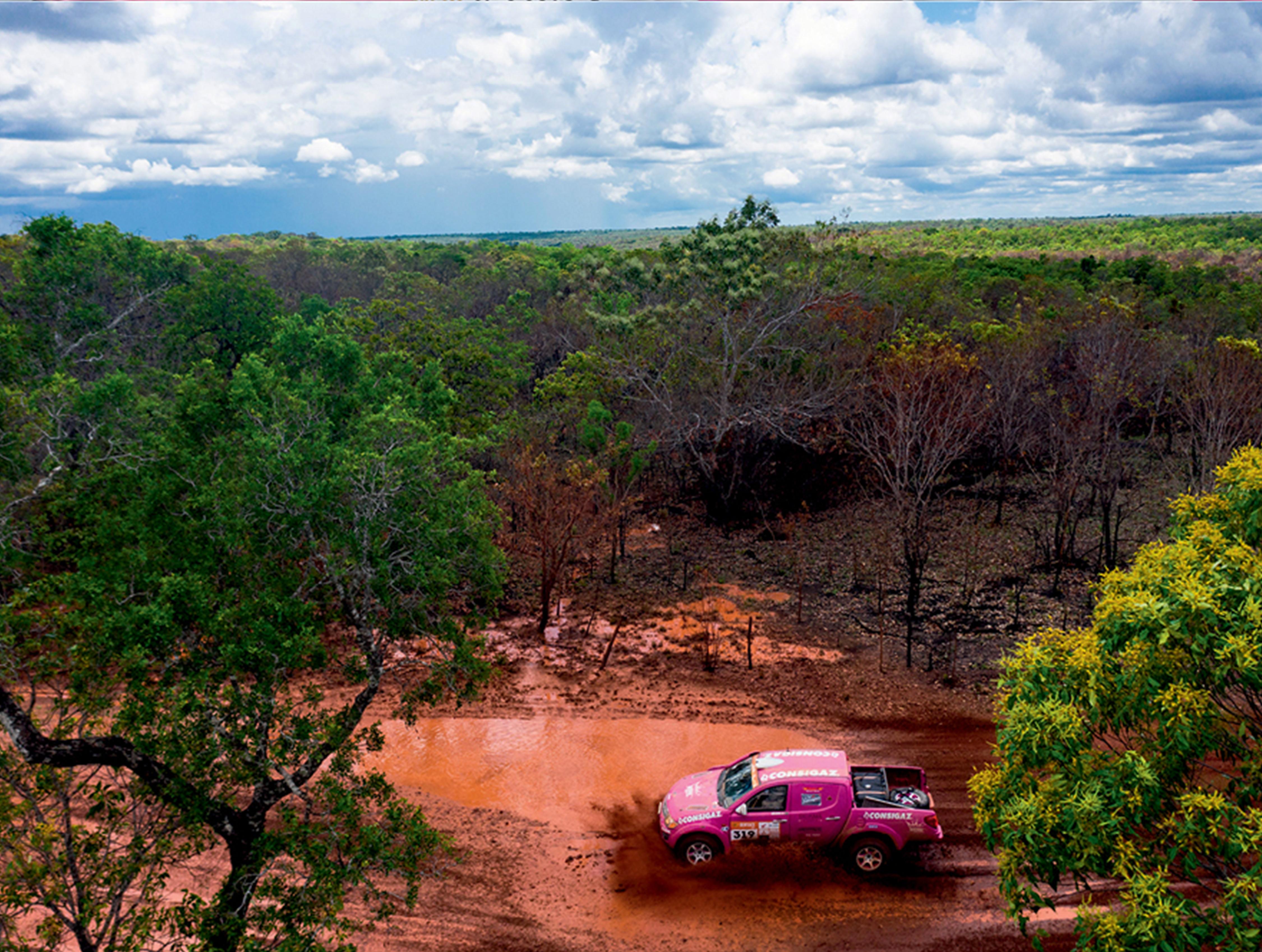 Numa pista lamacenta cercada por árvores surge uma caminhonete pink