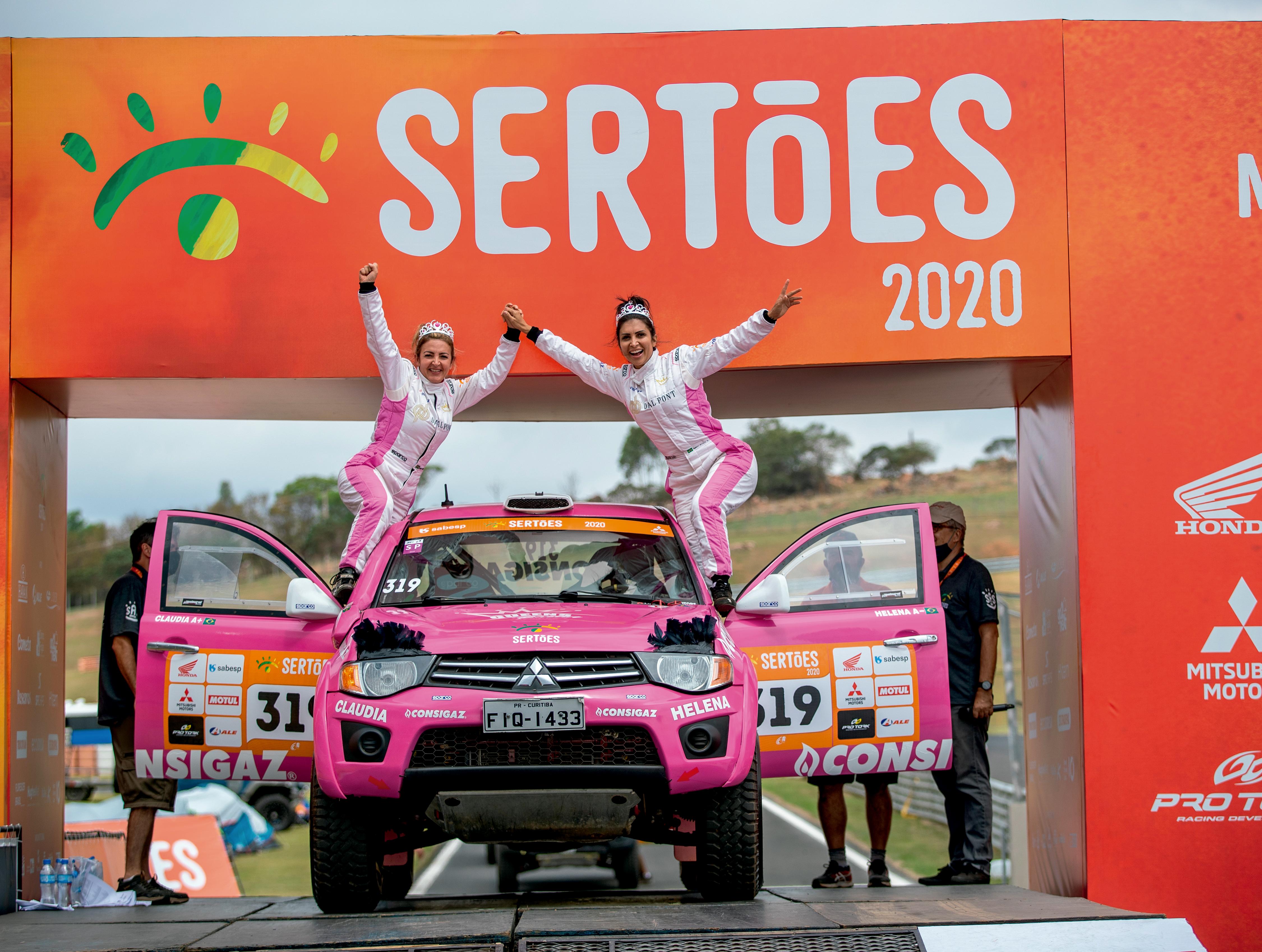 duas mulheres estão de pé apoiadas nas portas abertas de um carro cor de rosa. O farol do carro tem um item que imita cílios