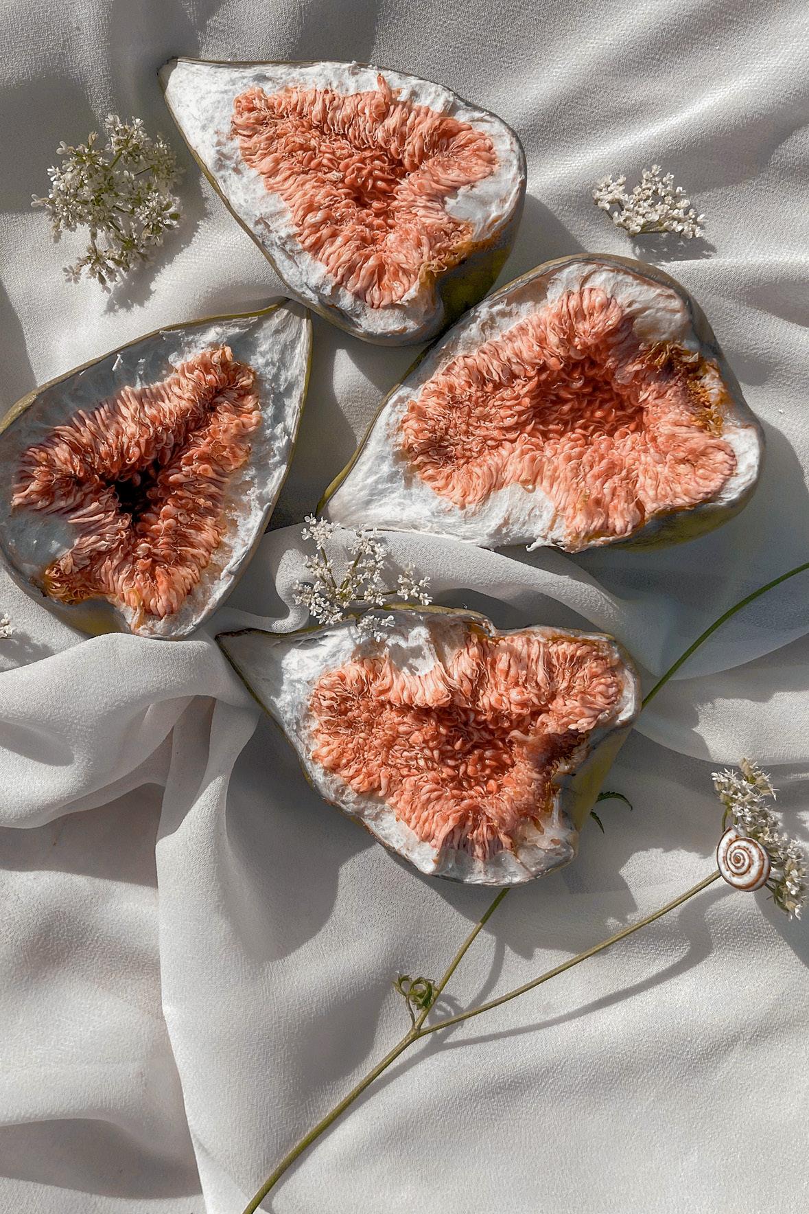 figos cortados ao meio sobre um tecido branco amassado e florzinhas