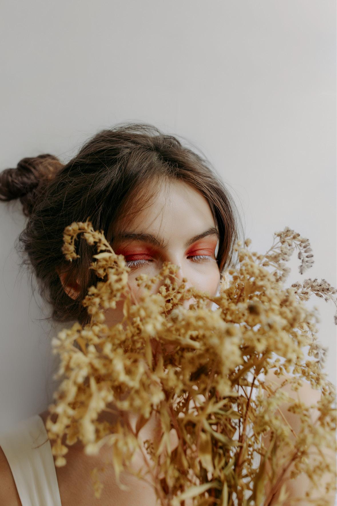 mulher branca com cabelo castanho preso em um coque está maquiada com sombra laranja e rímel branco. Ela segura um buquê de flores secas em frente ao rosto