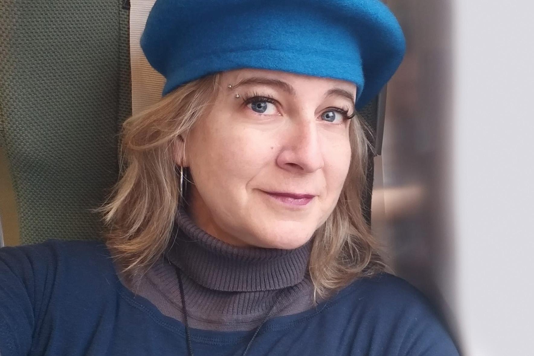 Selfie de mulher branca, com cabelos loiros curtos. Ela usa uma boina azul e uma blusa da mesma cor