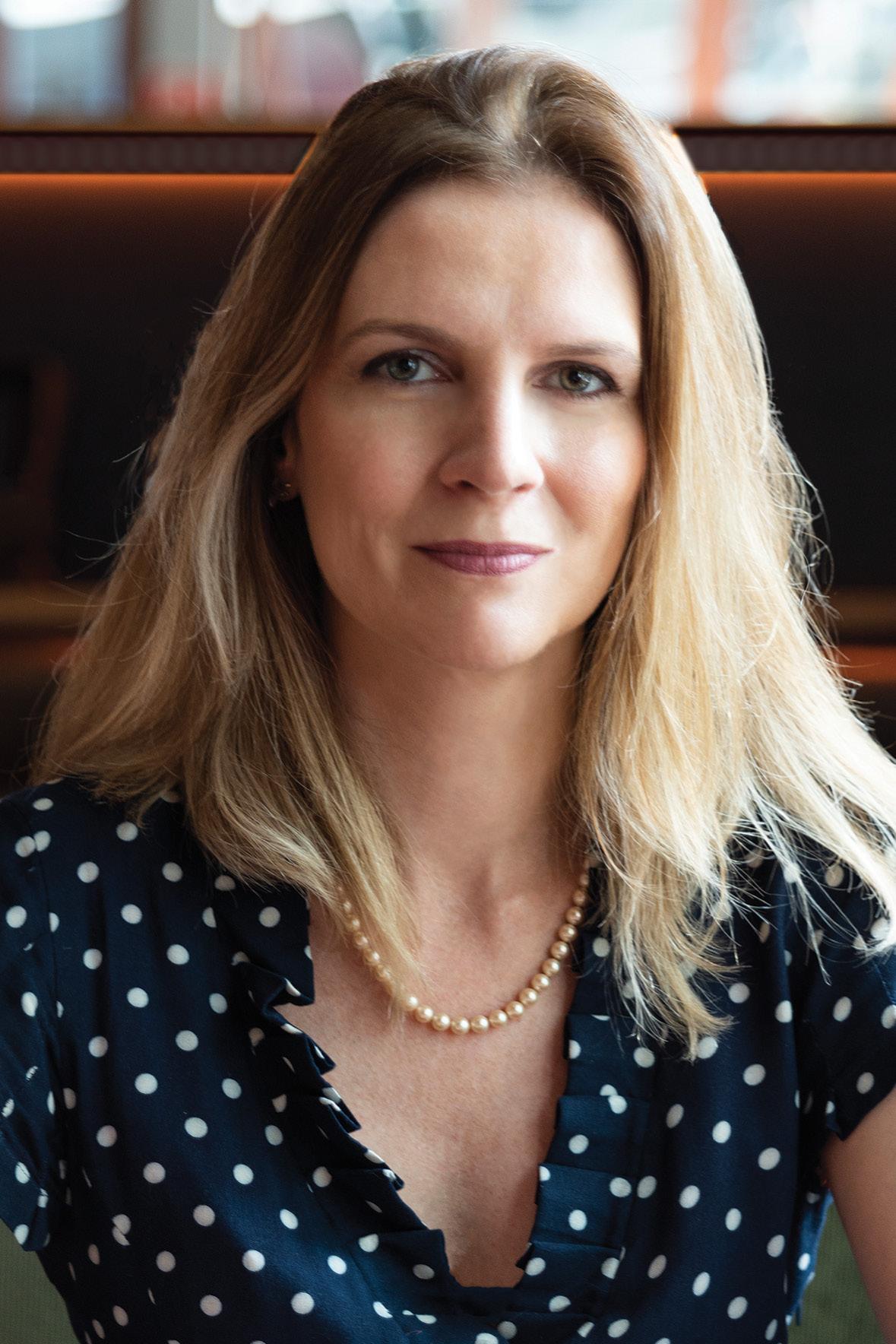 Mulher loira com blusa azul marinho de bolinhas brancas e colar de pérolas posa para foto, olhando para câmera