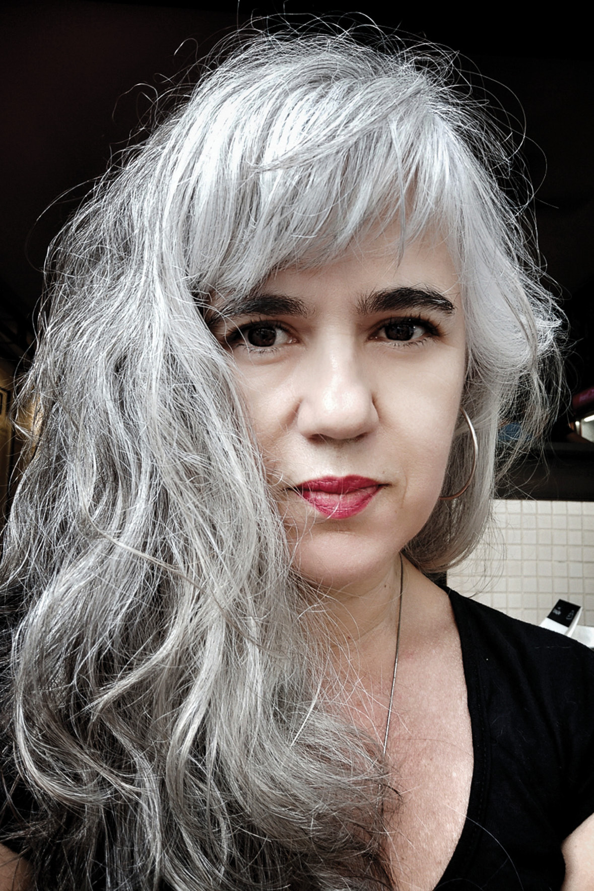 Mulher branca, de cabelos longos e grisalhos, vestindo uma bulsa preta olha para a câmera.