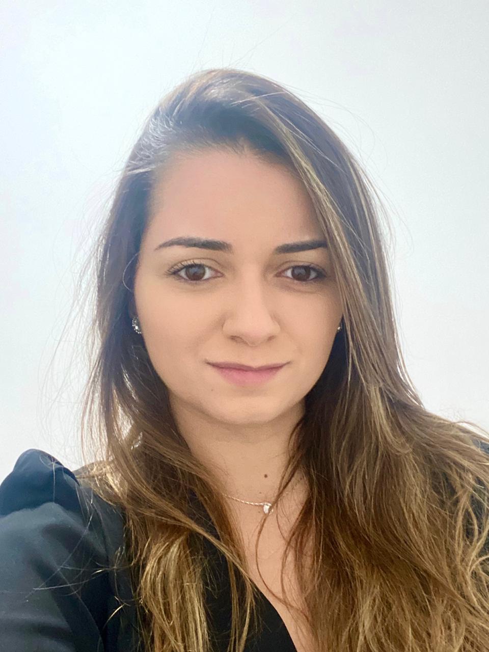 Mulher com cabelo castanho claro liso e blusa preta