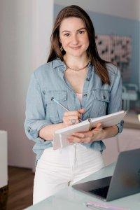 Lorena em pé com um caderno e caneta na mão