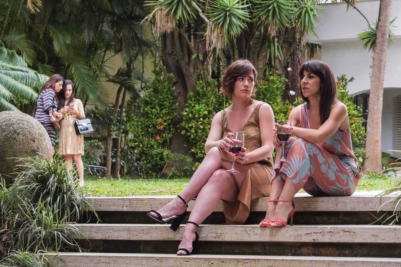 Duas mulheres estão sentadas nos degraus de uma escada ao ar livre