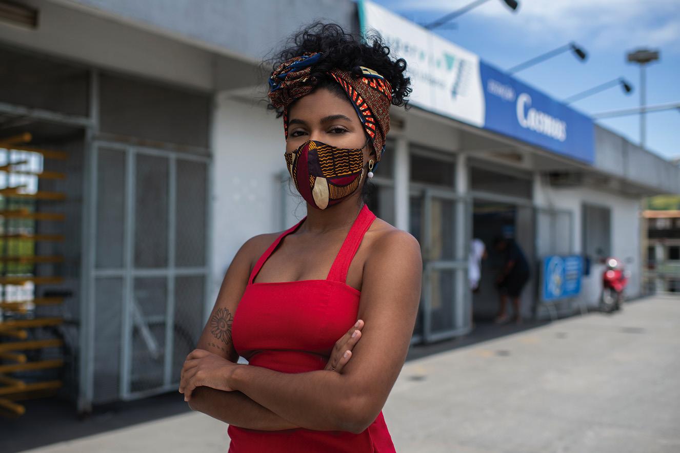 Joyce usa macacão vermelho, lenço no cabelo e máscara no rosto. Ela está com os braços cruzados em frente a uma instituição pública