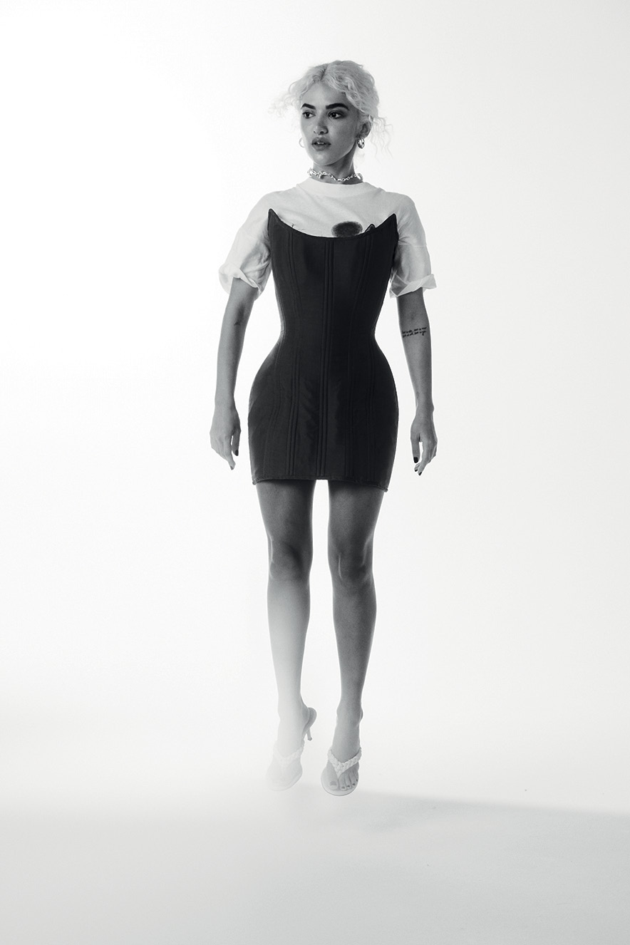 Manu Gavassi usando camiseta com vestido salta registrada pela câmera