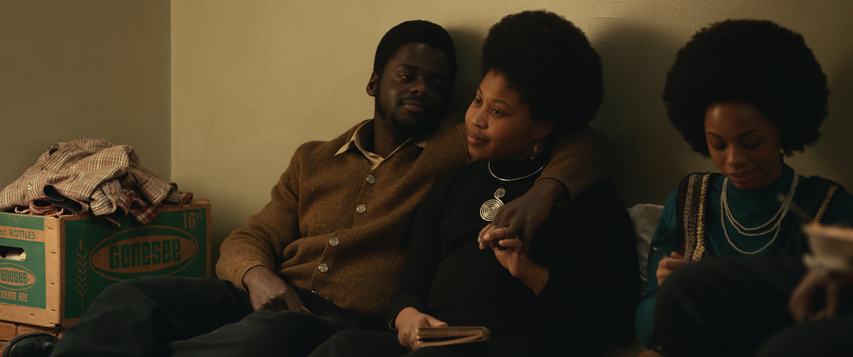 Foto do filme Judas e o Messias Negros. Um homem sentado ao lado de uma mulher passa o braço sobre seu pescoço