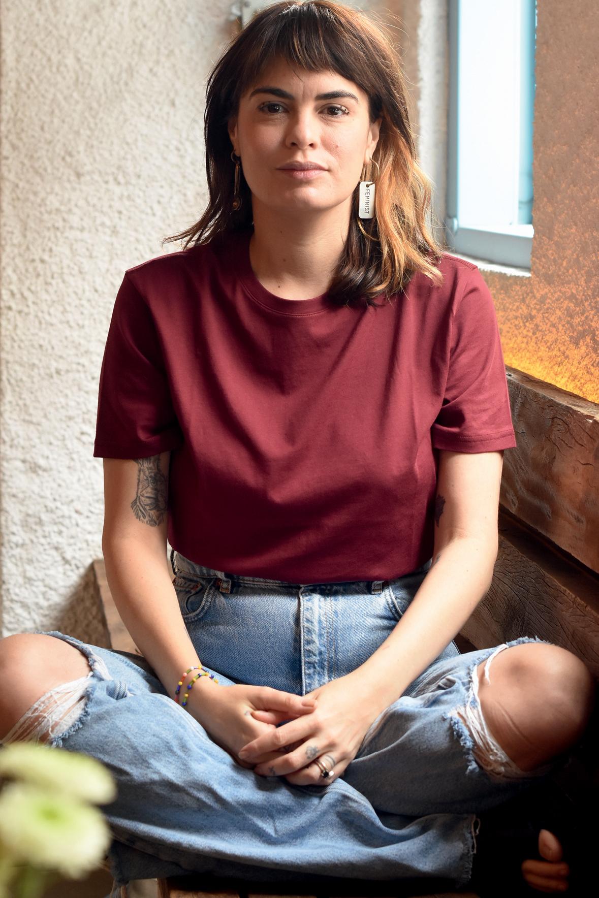Cafira é uma mulher de pele branca e cabelos castanho avermelhados na altura dos ombros. Ela usa uma calça jeans, camiseta vermelha e brincos grandes. Está sentada com as mãos sobre as pernas e olha para a câmera